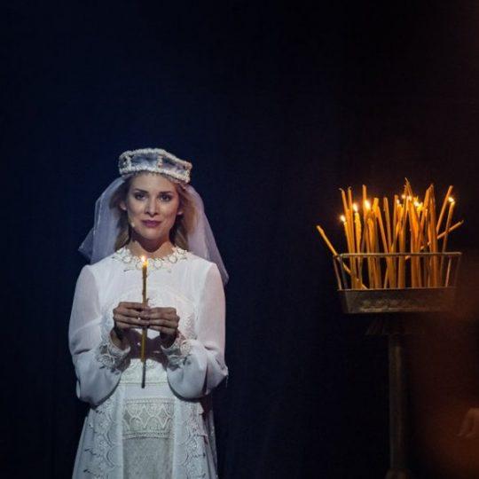 Na zdjęciu kobieta w białej, koronkowej sukience i w welonie. Trzyma w dłoniach zapaloną świeczkę. Po prawej stronie na stojaku stoi kilkadziesiąt świeczek, część z nich pali się.