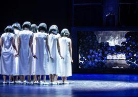 Kilka kobiet ubranych w białe sukienki stoi tyłem. Przed nimi duża gilotyna. Pod nią , za szybą kilkadziesiąt czaszek.