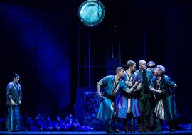 Scena oświetlona na niebiesko.Grupa mężczyzn stoi obok siebie, rozmawiając.Po lewej stronie stoi kobieta, która przygląda się im. W oddali siedzi kilkanaście osób.