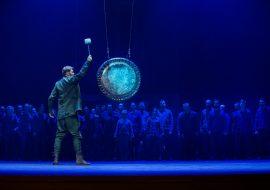 Scena oświetlona niebieskim światłem. Na środku stoi mężczyzna z ręką uniesioną do góry. Na linach wisi duży gong. W oddali w rzędzie stoi kilkadziesiąt kobiet i mężczyzn.