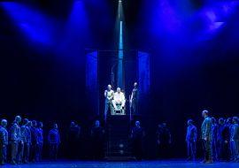 Scena oświetlona niebieskim światłem. Na środku , na metalowych schodach siedzi mężczyzna oświetlony łuną białego światła. Na dole , po obydwu stronach stoi kilkanaście osób . Wszyscy zwróceni w stronę schodów.
