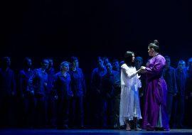 Kobieta ubrana w fioletowe kimono trzyma dłoń dziewczyna w białej sukience. Stoją zwrócone do siebie.Wokół kilkanaście osób przygląda im się.