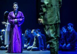 Na przodzie stoi kobieta ubrana w fioletowe kimono. Za nią siedzi kilka kobiet. Przed nią sylwetka mężczyzny w mundurze.