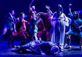 Kilka osób tańczy na scenie. Przed nimi, na boku leży mężczyzna. Za nim stoi kobieta w jasnej sukience. Scena oświetlona na niebiesko.