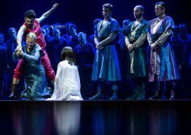 Po prawej stronie stoi trzech mężczyzn w płaszczach. Po lewej stronie klęczy kobieta, ciągnie rękę mężczyzny stojącego za nią. Na środku klęczy kobieta w jasnej sukience. Za nimi, stoi w rzędzie kilkanaście kobiet i mężczyzn.