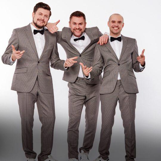 Trzech mężczyzn w garniturach w kratkę, białych koszulach i czarnych muszkach. Stoją obok siebie, uśmiechają się. Meżczyzna stojący w środku, trzyma ręcę na ramionach mężczyzn stojących obok.