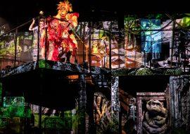 Na scenie dwupiętrowa konstrukcja z iluminacją świateł przypominającą dżunglę. Na piętrze, przy barierce chłopiec. Obok niego dwie osoby w kolorowych, powycinanych kostiumach.