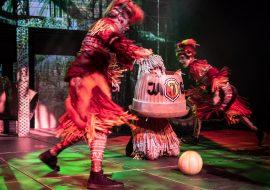 Na scenie dwupiętrowa konstrukcja z iluminacją świateł przypominającą dżunglę. Przed nią trzy osoby w powycinanych, czerwonych kostiumach. Na środku plastikowa, okrągła, otwarta bryła z napisem ''JAGA''. Z niej wystaje jedna z osób z włosami w kształcie powycinanych frędzli. Dookoła niej biegaja kobieta i mężczyzna. Na środku leży piłka.