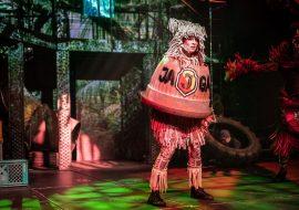 Na scenie dwupiętrowa konstrukcja z iluminacją świateł przypominającą dżunglę. Na środku stoi kobieta w kolorowym, powycinanym kostiumie. Ma nałozoną na siebie pomarańczową, plastikową bryłę z napisem ''JAGA''. Po prawej stronie, leży duża, gumowa opona, przyczepiona do wiszącego łańcucha. W niej siedzi chłopiec.