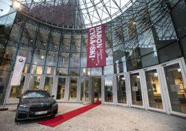 Wejście do Opery i Filharmonii Podlaskiej. Przed wejściem czerwony dywan.Po lewej stronie samochód marki BMW. Na górze zwisający w dół billboard z napisem: ''Baron cygański. Johann Strauss''.