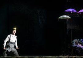 Na scenie półmrok. Po lewej stronie mężczyzna z łopatą w prawej dłoni. Ubrany w białą koszulę i spodnie na szelkach. Na głowie latarka. Po prawej stronie kolorowe, wysokie parasole. Część kolorowej kanapy.