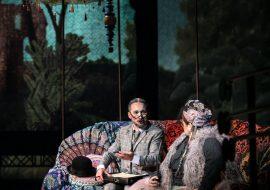 Kobieta i mężczyzna siedzą na sofie. Kobieta w kostiumie Cyganki , z chustką na głowie. Mężczyzna w garniturze w kratkę i okularach. Za nimi wysokie, kolorowe parasole.