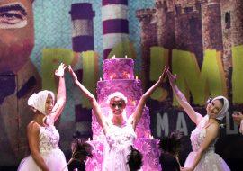 Na scenie duży, różowy tort z podświetlonymi świeczkami. Przed nim trzy kobiety w tiulowych sukienkach, z wyprostowanymi rękoma ku górze. Na podłodze sceny siedzi kobieta w tiulowej sukience.