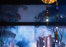 Na środku sceny kobieta w kostiumie Cyganki. Za nią, na billbordzie, zamek na wzgórzu. Nad sceną wiszą na linkach z koralików: księżyc, sowy.