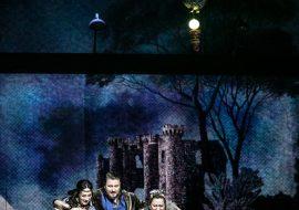 Na scenie półmrok. Dwie kobiety w kostiumach Cyganek i mężczyzna pochylają się nad złotą, otwartą szkatułą, stojącą na scenie. Mężczyzna obejmuje ramionami kobiety. Nad nimi wisi podświetlony księżyc z brelokiem w kształcie sowy. W oddali na billbordzie zamek nocą.