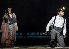 Na scenie dwie osoby. Po lewej kobieta w kostiumie Cyganki. W prawej ręce trzyma fajkę. Bliżej , po prawej stronie mężczyzna, klęczy na jednym kolanie. W białej koszuli, w szarych spodniach na szelkach. W prawej ręce trzyma łopatę. Na głowie ma świecącą latarkę.