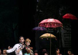 Po lewej stronie kobieta i mężczyzna, stoją blisko siebie przodem do widowni. Mężczyzna ubrany w różowe spodnie z szelkami i białą koszulę. Kobieta ubrana w białą spódnicę w falbany i bluzkę w hafty. Po prawej stronie kolorowa kanapa. Za nią kilka kobiet w kostiumach Cyganek. Pomiędzy nimi kolorowe, wysokie parasole.