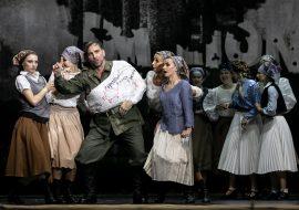Na scenie mężczyzna w mundurze wojskowym z lewą ręką i tułowiem w gipsie. Prawą rękę trzyma w górze z uniesionym palcem wskazującym. Wokół niego kilka kobiet w kostiumach wieśniaczek, w chustkach na głowie.