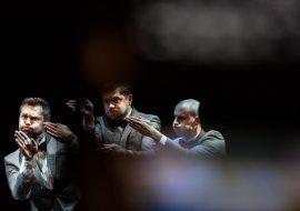 Trzech mężczyzn z uniesionymi do ramion rękoma, dłonie złożone, skierowane przed siebie. Usta wypełnione powietrzem.