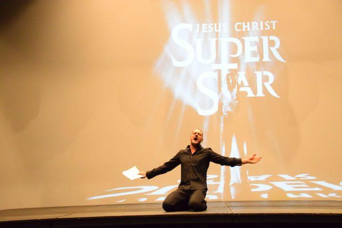 """Krzysztof Gorczak bierze udział w castingu do spektaklu """"Jesus Christ Superstar"""". Ubrany w ciemne kolory klęczy na ziemi, ma rozłożone ręce, w prawej trzyma partyturę, śpiewa fragment piosenki ze spektaklu. W tle widoczny jest biały logotyp spektaklu """"Jesus Christ Superstar"""" na pomarańczowym tle."""
