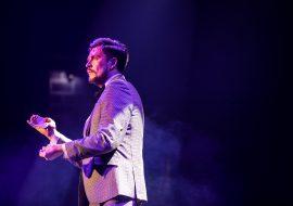 Na scenie mężczyzna w garniturze oświetlony fioletowym światłem. W prawej dłoni trzyma talię kart.