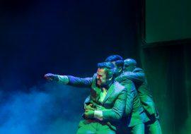 Scena słabo oświetlona, w oddali dym. Na scenie trzech mężczyzn w garniturach. Stoją w rzędzie za sobą, trzymając się rękoma. Pierwszy z nich trzyma wyciągniętą rękę do przodu.