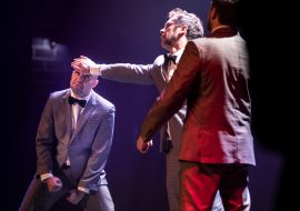 Na scenie trzech mężczyzn w garniturach. Mężczyzna stojący pośrodku, trzyma rękę na czole mężczyzny po lewej stronie.