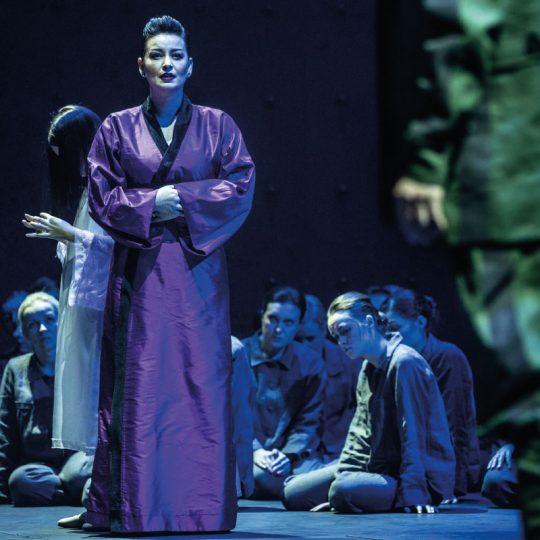 Na przodzie stoi kobieta w fioletowym kimonie. Za nią siedzi kilka kobiet.